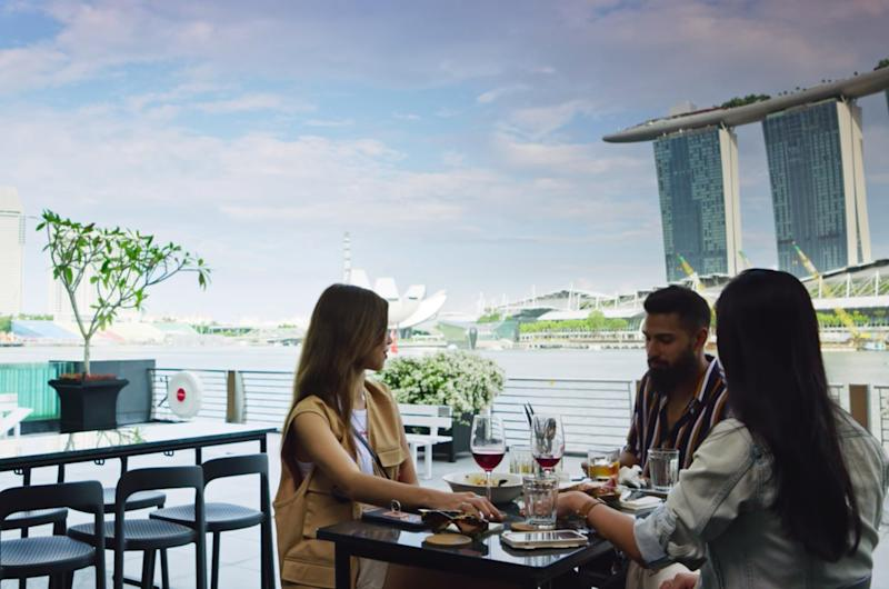 """(Left to right) Mae Tan, Vinny Sharp and Nicole Ong by the Singapore River and Marina Bay Sands in Netflix's reality TV series """"Singapore Social""""."""