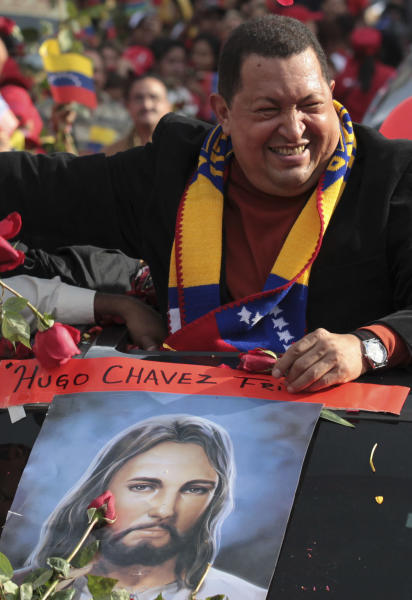 FILE - In this Feb. 24, 2012 file photo, Venezuela's President Hugo Chavez greets supporters during his caravan from Miraflores presidential palace to the airport to travel to Cuba for surgery to remove a tumor, in Caracas, Venezuela. The poster shows an image of Jesus Christ. Chavez has spent much of his career praising the socialist ideas of famed atheists such as Karl Marx and Fidel Castro. However, now in the thick of a prolonged battle against cancer, Chavez is drawing inspiration more than ever from Jesus Christ. (AP Photo/Fernando Llano, File)