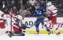 Carolina Hurricanes goalie Petr Mrazek (34), of the Czech Republic, makes a save as Vancouver Canucks' Tanner Pearson (70) and Carolina's Brett Pesce (22) watch during the first period of an NHL hockey game in Vancouver, British Columbia, Thursday Dec. 12, 2019. (Darryl Dyck/The Canadian Press via AP)