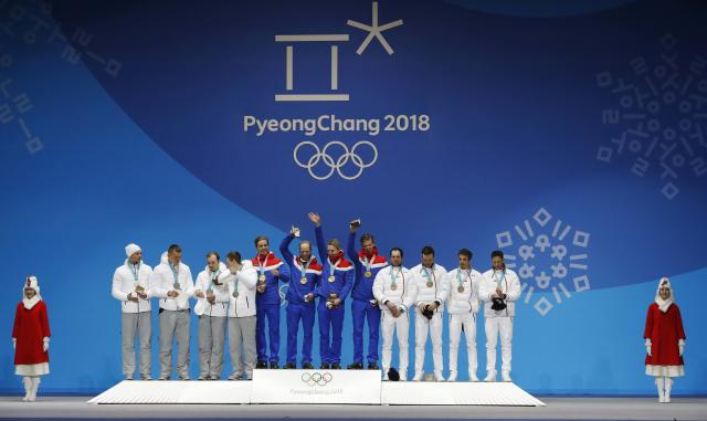 Medals Ceremony - Cross-Country Skiing - Pyeongchang 2018 Winter Olympics - Men's 4x10 km Relay - Medals Plaza - Pyeongchang, South Korea - February 18, 2018 - Gold medalists Didirk Toenseth, Johnsrud Martin Sundby, Simen Hegstad Kreuger and Johannes Hoesflot Klaebo of Norway, silver medalists Andrey Larkov, Alexander Bolshunov, Alexey Chervotkin and Denis Spitsov, Olympic athletes from Russia, and bronze medalists Jean Marc Gaillard, Maurice Manificat, Clement Parisse and Adrien Backsheider of France on the podium. REUTERS/Eric Gaillard
