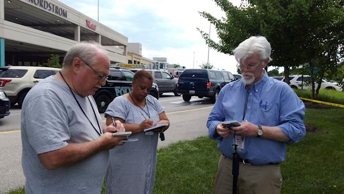 Journalist E.B Furgurson, right, takes notes with two other people as police officers respond.