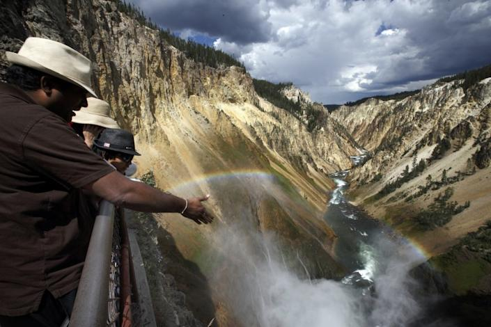Visitors view the Yellowstone River from an observation deck above Lower Falls in the Grand Canyon of Yellowstone National Park.