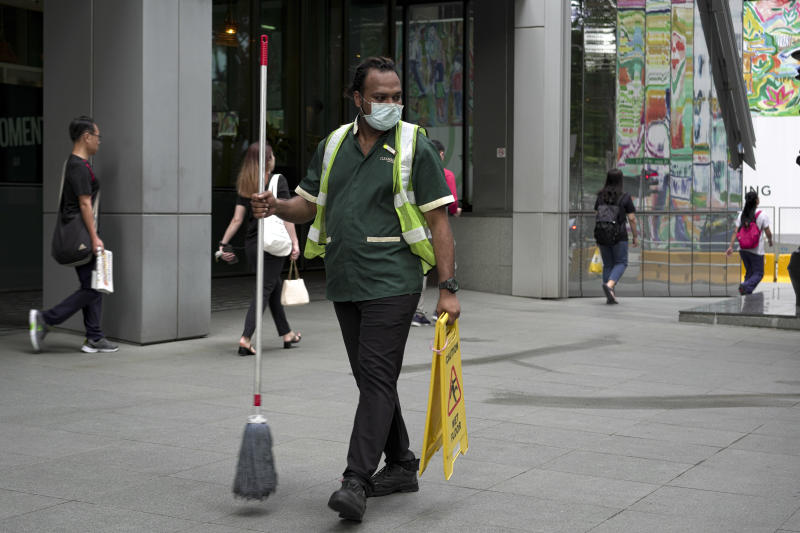 SINGAPORE, SINGAPORE - FEBRUARY 28: A maintainance worker wearing a mask walks past the Central Business District on February 28, 2020 in Singapore. The coronavirus, originating in Wuhan, China has spread to over 80,000 people globally, more than 50 countries have now been infected. (Photo by Ore Huiying/Getty Images)