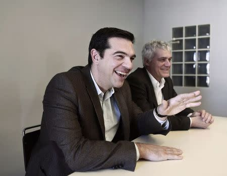 Tsipras, opposition leader and head of radical leftist Syriza party, smiles during a meeting with members of the Greens-Ecologists party, at the party's headquarters in Athens