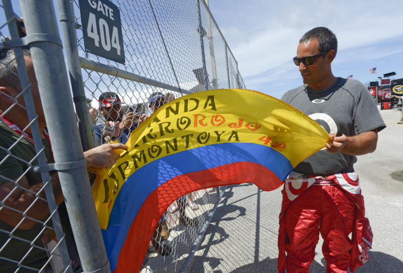 Juan Pablo Montoya, of Colombia, signs a flag for a fan before a racing practice session for the NASCAR Sprint Cup auto race at Daytona International Speedway Thursday, July 4, 2013, in Daytona Beach, Fla. (AP Photo/Phelan M. Ebenhack)