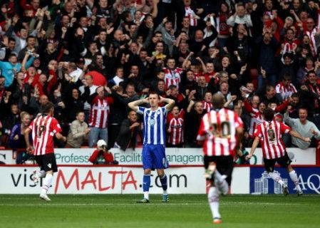 Sheffield Wednesday's Chris Lines stands dejected as Sheffield United's Ched Evans (right) celebrates scoring their second goal of the game
