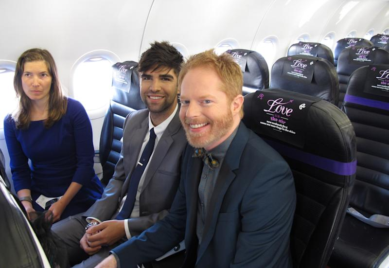 """Jesse Tyler Ferguson, right, star of the ABC sitcom """"Modern Family,"""" and husband Justin Mikita attend the airborne wedding of Lynley Bendall and Ally Wanikau Monday, Aug. 19, 2013, on a flight that left from Queenstown, New Zealand. A law change allowed same-sex couples to marry in New Zealand for the first time Monday. The couple celebrated the legalization of gay marriage in New Zealand by getting hitched in a plane at 39,000 feet (11,900 meters). Their wedding was held in the air after they won a promotion by national carrier Air New Zealand. (AP Photo/Nick Perry)"""