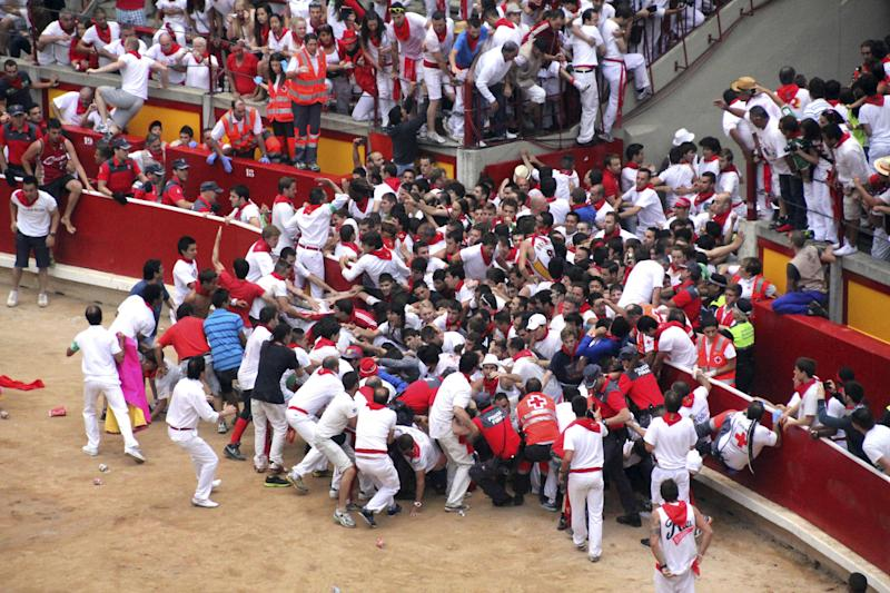 Runners trip and fall ahead of the bulls blocking the entrance of the bullring during the running of the bulls of the San Fermin festival, in Pamplona, Spain, Saturday, July 13, 2013. A total of 21 people have been injured, two by gorings, as thousands of daredevils raced through the crowded streets of Pamplona in a hair-raising running of the bulls that ended in a crush on Saturday. (AP Photo/Joseba Etxeberria)
