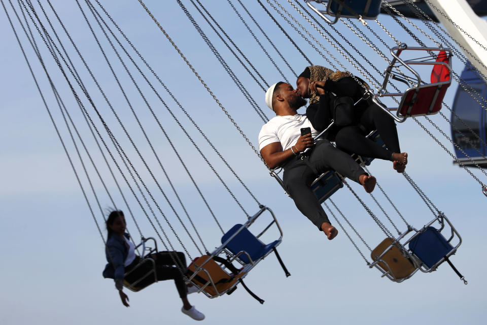 Arif El-Boukari, left and Buthaina Ali, from Detroit, shares a kiss while riding the wave swinger during their Eid Al Fitr holiday, Friday, May 14, 2021 in Navy Pier, Chicago. The U.S. Centers for Disease Control and Prevention eased its guidelines on the wearing of masks outdoors, saying fully vaccinated Americans don't need to cover their faces anymore unless they are in a big crowd of strangers. (AP Photo/Shafkat Anowar)