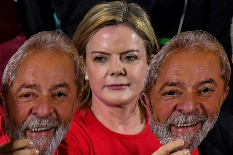 Gleisi Hoffmann, the head of jailed ex-president Luiz Inacio Lula da Silva's Workers Party, holding masks of the former leader, whose appeal against disqualification in October elections has been rejected by the Supreme Court