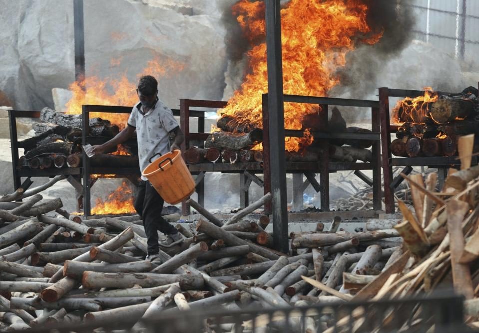 A worker sprinkles fuel on burning funeral pyres