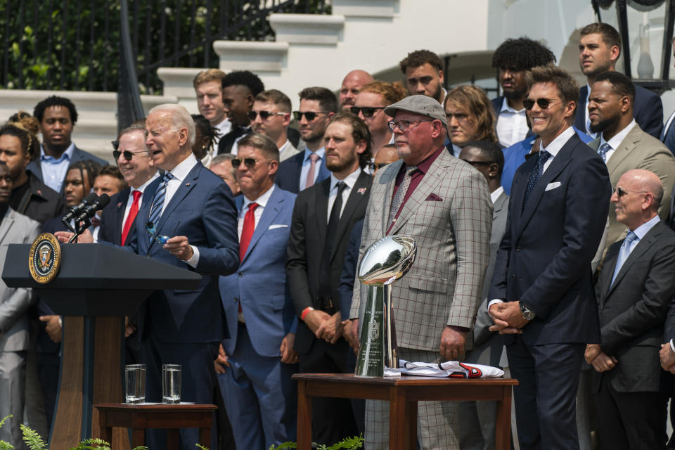 President Joe Biden, surrounded by members of the Tampa Bay Buccaneers including Tom Brady, right, speaks during a ceremony on the South Lawn of the White House, in Washington, Tuesday, July 20, 2021, where the president honored the Super Bowl Champion Tampa Bay Buccaneers for their Super Bowl LV victory. (AP Photo/Manuel Balce Ceneta)