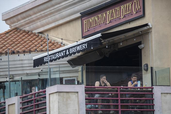 "Patrons relax at Huntington Beach Beer Co. Lost business at bars and restaurants amid the pandemic has in turn hurt suppliers and distributors, leaving them vulnerable to closures or takeovers. <span class=""copyright"">(Allen J. Schaben / Los Angeles Times)</span>"