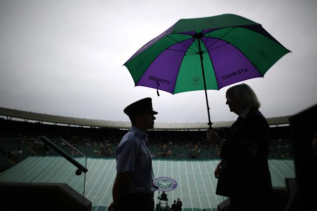 LONDON, ENGLAND - JUNE 27: A steward (R) waits under an umbrella as rain interupts play on court one on day four of the Wimbledon Lawn Tennis Championships at the All England Lawn Tennis and Croquet Club on June 27, 2013 in London, England. Play has been disrupted due to rain. (Photo by Peter Macdiarmid/Getty Images)