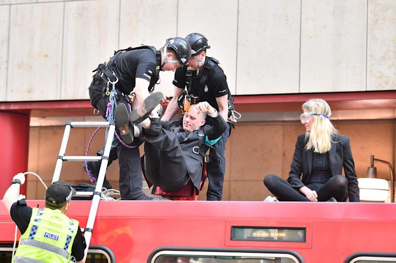 A protester is removed from the roof of a DLR train (AFP/Getty Images)