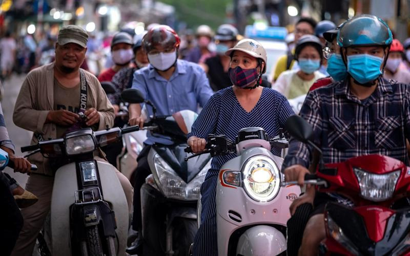 Motorcyclists wearing protective masks sit in traffic in Hanoi, Vietnam - Bloomberg