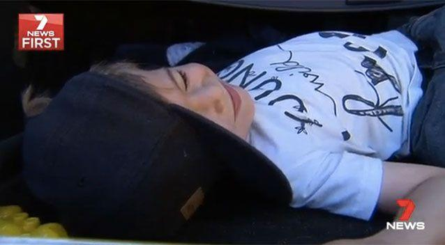 Tyler shows how he was lying in his mum's car. Picture: 7 News