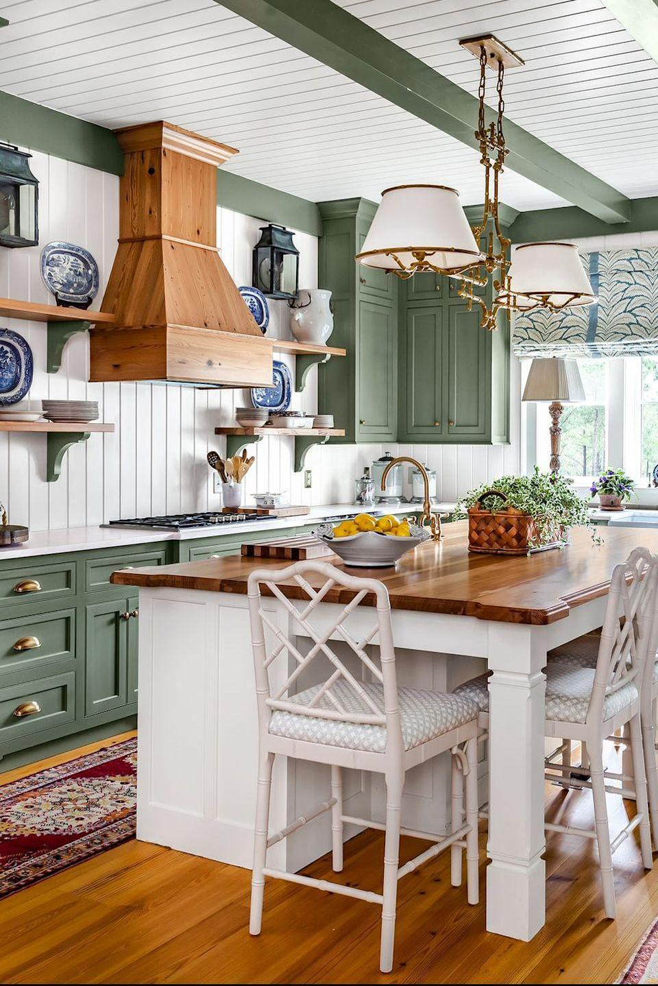 <p>Bright white wood panels, which are also used on the ceiling, give this rustic kitchen a cohesive look.</p>