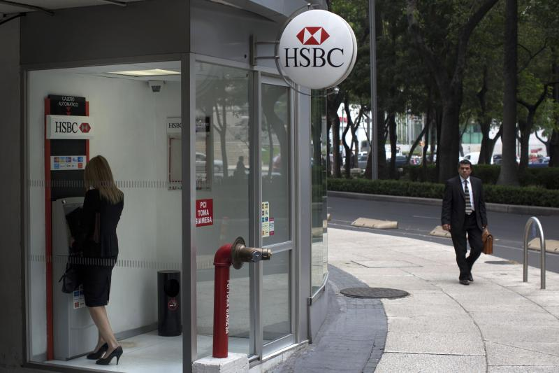 A woman uses a cash machine at the HSBC bank headquarters in Mexico City, Wednesday, July 25, 2012.  Mexican regulators have levied a $28 million fine against the Mexico subsidiary of London-based HSBC bank for failing to prevent money laundering through accounts at the bank. (AP Photo)