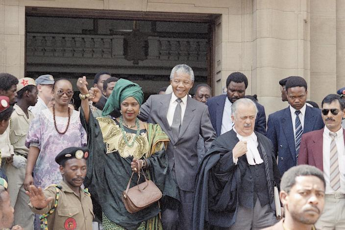 <p>Winnie Mandela, left, wife of African National Congress leader Nelson Mandela, center right, leaves the Rand Supreme Court on Feb. 13, 1991, after an adjournment after two key state witnesses, fearing for their safety, refused to testify in the case in which Mrs. Mandela is charged with kidnapping and assault. (Photo: AP) </p>