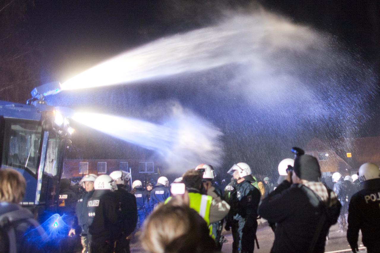 METZINGEN, LOWER SAXONY - NOVEMBER 24:  German police use water canons against anti-nuclear activists as they protest against the transport of nuclear waste on November 24, 2011 in Metzingen, Germany. A train carrying the Castor containers of processed, spent nuclear fuel is due to start from La Hague in France today for its journey to the Gorleben temporary nuclear waste storage facility in Germany, and thousands of protesters are expected to attempt to blockade the route.  (Photo by Carsten Koall/Getty Images)