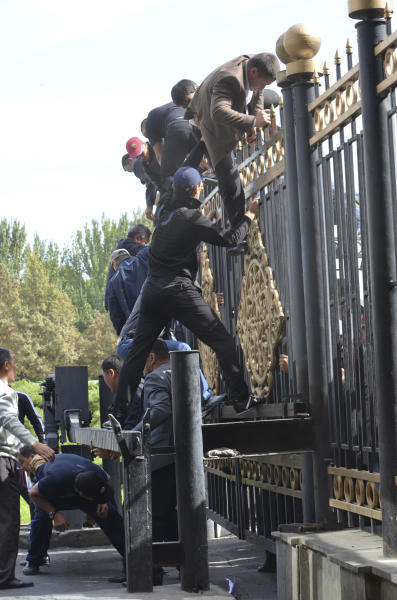 Supporters of Kamchibek Tashiyev scale over a fence surrounding government headquarters in downtown Bishkek, Kyrgyz capital on Wednesday, Oct. 3, 2012. Around 1,000 people gathered in the center of the city for a rally, organized by nationalist politicians Sapar Zhaparov and Kamchibek Tashiyev, ostensibly to demand the nationalization of a controversial gold mine in the east of the Central Asian nation. Police officers protecting the government building, known as the White House, used dogs and smoke bombs to disperse a group of young men who attempted to scale the gates. (AP Photo/ Abylay Saralayev)