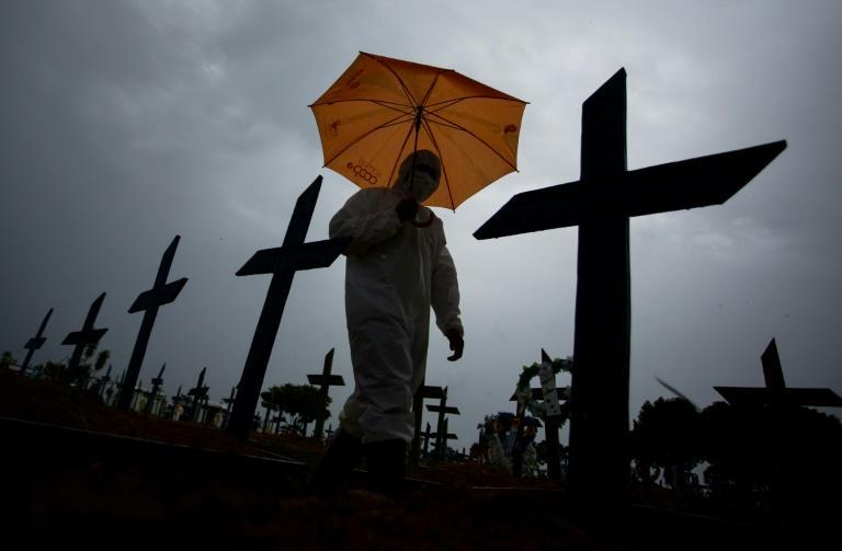 In this file photo taken on February 25, 2021 a worker wearing a protective suit and carrying an umbrella walks past the graves of Covid-19 victims at the Nossa Senhora Aparecida cemetery, in Manaus, Brazil