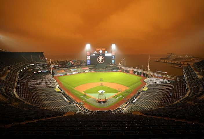 """Smoke from wildfires obscures the sky over Oracle Park in San Francisco as the Seattle Mariners take batting practice before their baseball game against the San Francisco Giants on Sept. 9, 2020. <span class=""""copyright"""">(Tony Avelar / Associated Press)</span>"""