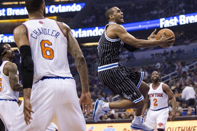 Orlando Magic's Arron Afflalo, center, drives to the basket while defended by New York Knicks' Tyson Chandler (6) and Raymond Felton (2) during the first half of an NBA basketball game in Orlando, Fla., Friday, Feb. 21, 2014. (AP Photo/Willie J. Allen Jr.)