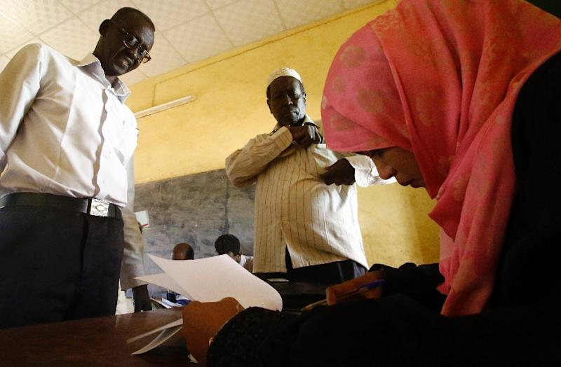 A Sudanese member of the electoral committee checks a voters details at a polling station at the Al-Daim East school in the capital, Khartoum, on April 13, 2015 (AFP Photo/Ashraf Shazly)