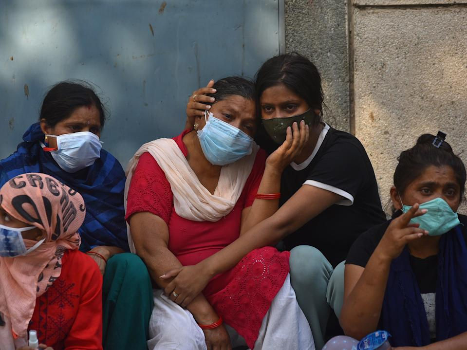 <p>Grieving family members of COVID-19 victims at a cremation ground in New Delhi, India, 29 April 2021. Delhi High Court judges on Thursday tore into the Centre for claiming capital has sufficient oxygen supplies. </p> (EPA/IDREES MOHAMMED)