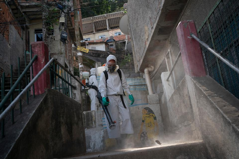 A volunteer sprays disinfectant in an alleyway to help contain the spread of the new coronavirus at the Babilonia slum of Rio de Janeiro, Brazil, Sunday, July 12, 2020. (AP Photo/Leo Correa)
