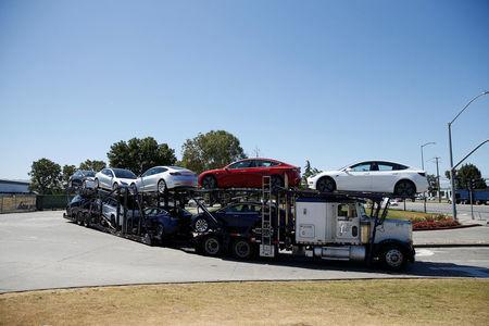 A car carrier trailer carries Tesla Model 3 electric sedans, is seen outside the Tesla factory in Fremont, California, U.S. June 22, 2018. REUTERS/Stephen Lam