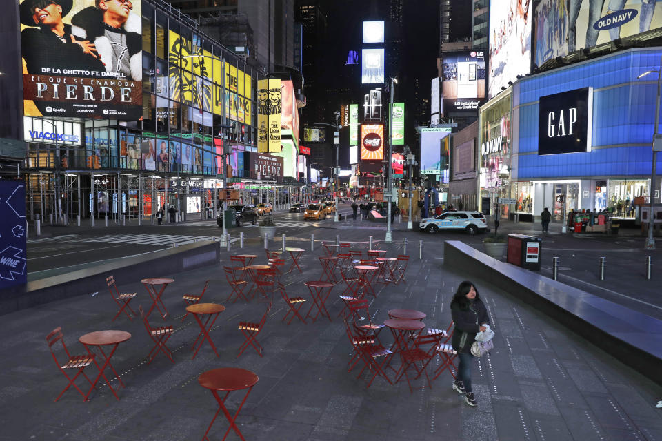 A woman walks through a lightly trafficked Times Square in New York, Monday, March 16, 2020. Bars and restaurants will become takeout-only and businesses from movie theaters and casinos to gyms and beyond will be shuttered Monday night throughout New York, New Jersey and Connecticut because of the coronavirus, the states' governors said. (AP Photo/Seth Wenig)
