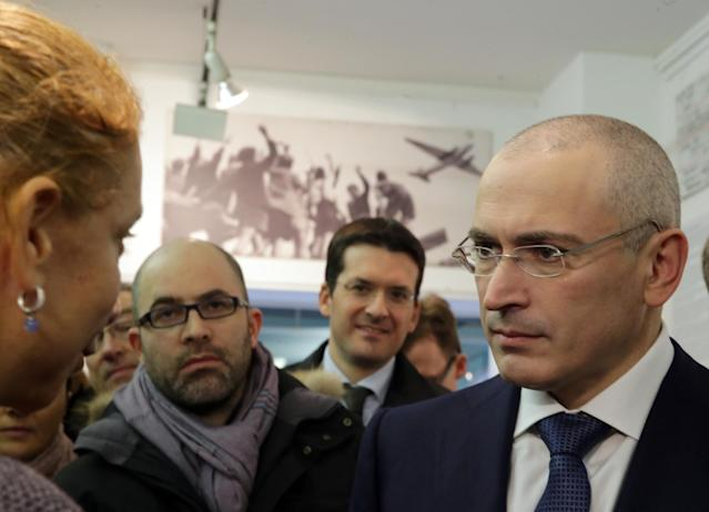 CORRECTS NAME OF MUSEUM - Mikhail Khodorkovsky, right, listens to Alexandra Hildebrandt, left, the curator of the Berlin Wall Museum , Haus am Checkpoint Charlie, as he arrives for a press conference at the museum in Berlin, Sunday Dec. 22, 2013. The former oil baron Mikhail Khodorkovsky was reunited with his family in Berlin on Saturday, a day after being released from a decade-long imprisonment in Russia. Khodorkovsky, a prominent critic of Russian President Vladimir Putin, was meeting with his eldest son Pavel and his parents, Marina and Boris, who had flown separately to the German capital to meet him (AP Photo/dpa, Kay Nietfeld)