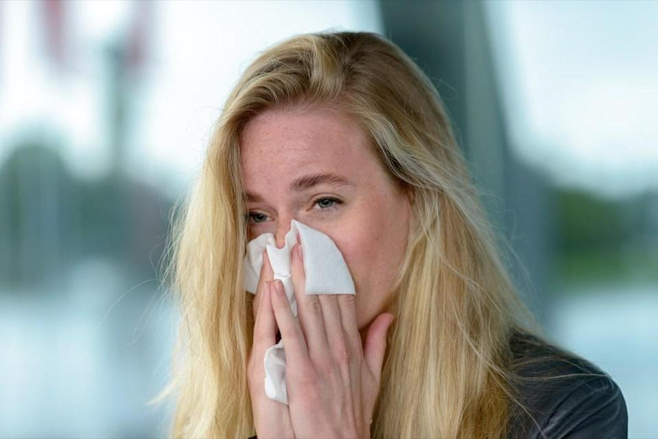 Woman blowing her nose into tissue