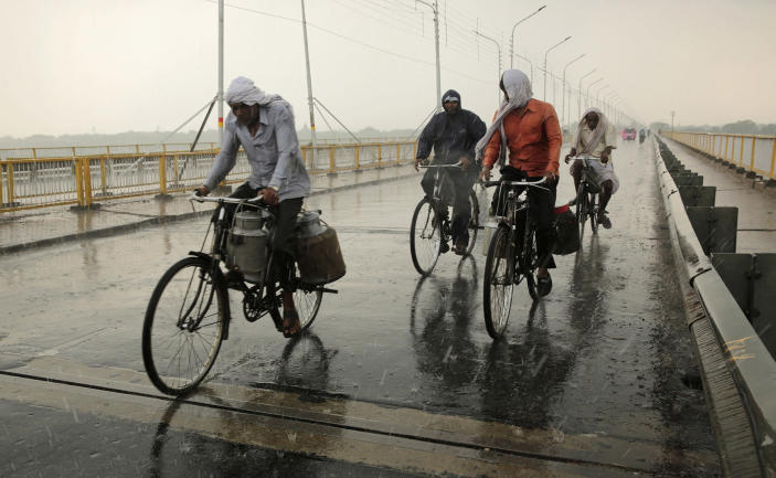 <p>Indians pedal past a bridge in the rain in Allahabad, India, July 8, 2016. Monsoon season in India begins in June and ends in October. (Photo: Rajesh Kumar Singh/AP) </p>