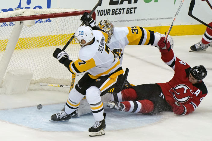 Pittsburgh Penguins center Colton Sceviour (7) and goaltender Tristan Jarry (35) defend against a shot by New Jersey Devils left wing Miles Wood (44) who fell to the ice while scoring a goal during the first period of an NHL hockey game, Sunday, April 11, 2021, in Newark, N.J. (AP Photo/Kathy Willens)