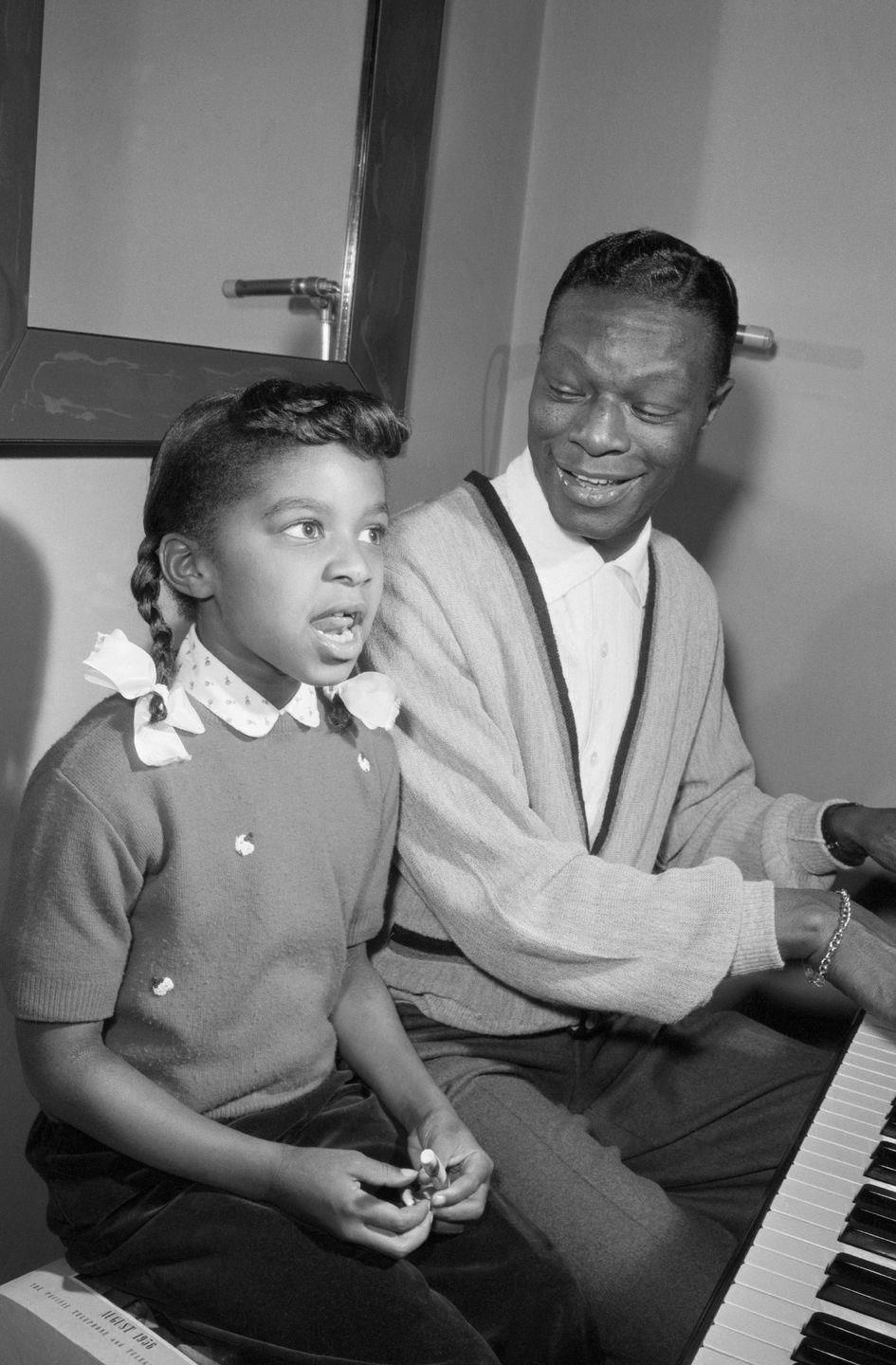 <p>Nat King Cole gives his 7-year-old daughter, Natalie, a voice lesson at the piano in their home in Los Angeles in December 1956.</p>