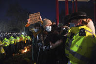A woman reacts in Clapham Common, as people gather despite the Reclaim These Streets vigil for Sarah Everard being officially cancelled, in London, Saturday, March 13, 2021. A serving British police officer accused of the kidnap and murder of a woman in London has appeared in court for the first time. Wayne Couzens, 48, is charged with kidnapping and killing 33-year-old Sarah Everard, who went missing while walking home from a friend's apartment in south London on March 3. (Victoria Jones/PA via AP)