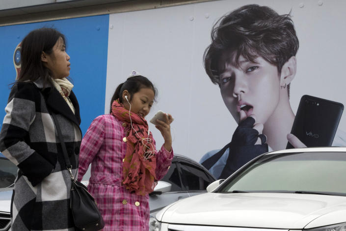 """FILE - In this Oct. 21, 2017, file photo, Chinese women walk past advertisement featuring teen idol Lu Han, also known as China's Justin Bieber in Beijing. China's government banned effeminate men on TV and told broadcasters Thursday, Sept. 2, 2021 to promote """"revolutionary culture,"""" broadening a campaign to tighten control over business and society and enforce official morality. (AP Photo/Ng Han Guan, File)"""