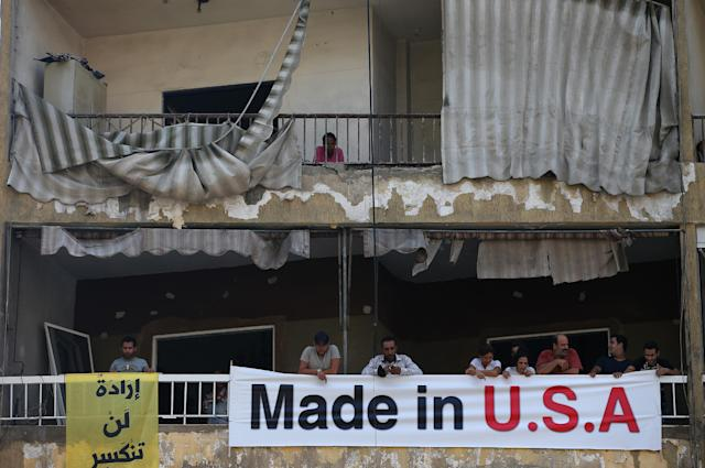 """Lebanese citizens stand behind an anti-US banner attached to their damaged balcony, at the site of a car bomb in a predominantly Shiite area and stronghold of the Lebanese militant group Hezbollah, in a southern suburb of Beirut, Lebanon, Friday, Aug. 16, 2013. Lebanese forensic experts collected evidence Friday at the scene of a massive explosion in a southern suburb of Beirut that killed dozens of people and wounded hundreds, the deadliest blast in the area in nearly three decades. The Arabic banner in the left reads, """"Will not break."""" (AP Photo/Hussein Malla)"""