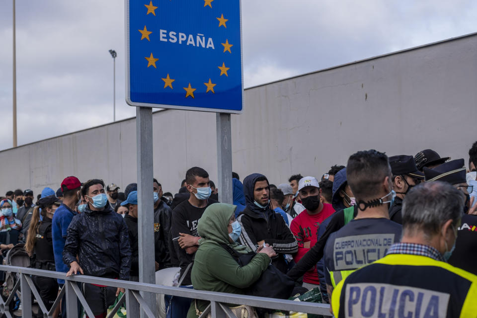 Moroccans, including many that have been in the Spanish enclave of Ceuta since before the border crisis, wait at the border to return voluntarily to their home country, Thursday, May 20, 2021. (AP Photo/Bernat Armangue)