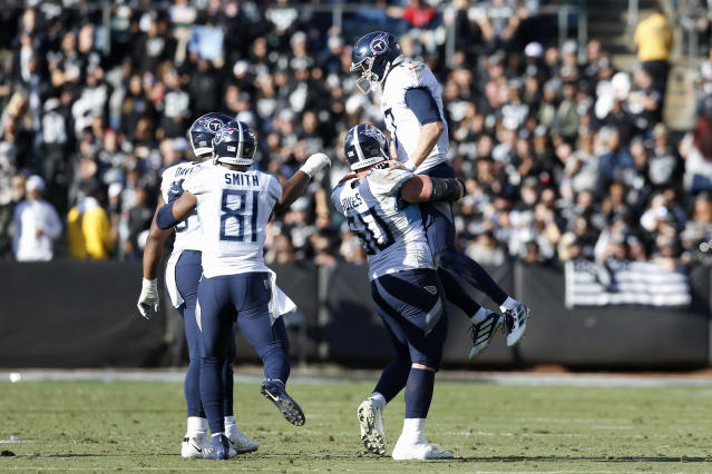 Tennessee Titans quarterback Ryan Tannehill, top, celebrates with teammates after throwing a touchdown pass to wide receiver A.J. Brown against the Oakland Raiders during the first half of an NFL football game in Oakland, Calif., Sunday, Dec. 8, 2019. (AP Photo/D. Ross Cameron)