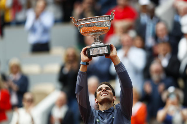 Spain's Rafael Nadal lifts the trophy as he celebrates his record 12th French Open tennis tournament title after winning his men's final match against Austria's Dominic Thiem in four sets, 6-3, 5-7, 6-1, 6-1, at the Roland Garros stadium in Paris, Sunday, June 9, 2019. (AP Photo/Pavel Golovkin)