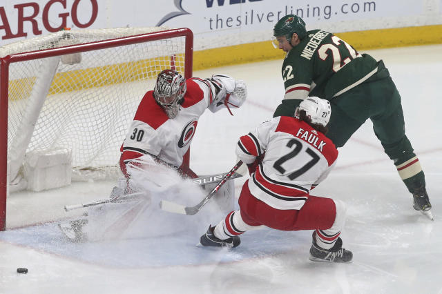 Carolina Hurricanes' goaltender Cam Ward , left, thwarts a scoring try by Minnesota Wild's Nino Niederreiter, right, of Switzerland in the first period of an NHL hockey game Tuesday, March 6, 2018, in St. Paul, Minn. (AP Photo/Jim Mone)