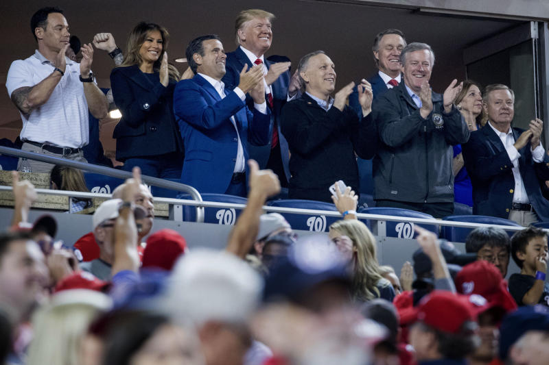 President Donald Trump, accompanied by first lady Melania Trump, second from left, and Republican lawmakers, stand during a Salute to the Military during Game 5 of a baseball World Series game between the Houston Astros and the Washington Nationals at Nationals Park in Washington, Sunday, Oct. 27, 2019. Also Pictured are Rep. John Ratcliffe, R-Texas, third from left, Sen. Lindsey Graham, R-S.C., right, Sen. David Perdue, R-Ga., fourth from right, and Rep. Mark Meadows, R-N.C., third from right. (AP Photo/Andrew Harnik)