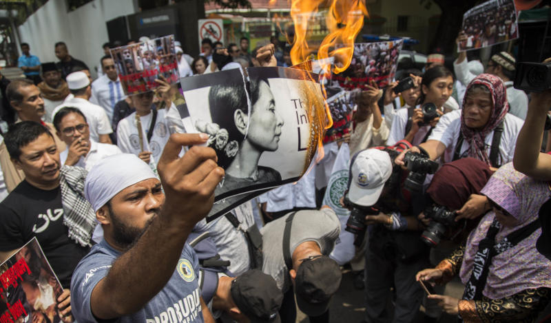 An Indonesian protester burns a picture of Suu Kyi during a rally in front of the Myanmar embassy in Jakarta on Sept. 2.
