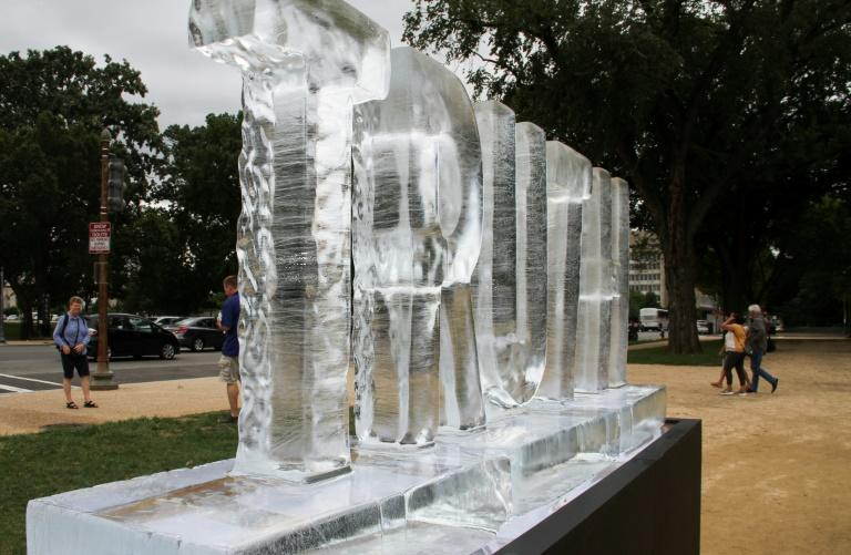 "People walk past LigoranoReese's ""Truth Be Told"" ice sculpture"