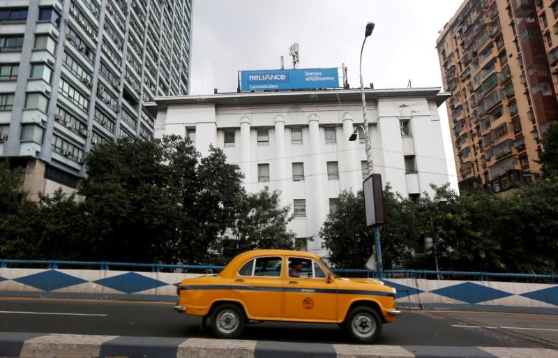 FILE PHOTO: A taxi drives past a Reliance Communications, controlled by billionaire Anil Ambani, office building in Kolkata